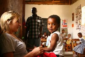 A volunteer spends time with a child at a care center in Tanzania.