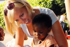 A volunteer reads to a child at a nursery in Togo.