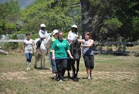 A volunteer leads a child on a horse at the Equine Therapy Project in South Africa.