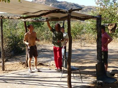 Volunteers on the Conservation & Environment project in South Africa construct a tent for wildlife observations