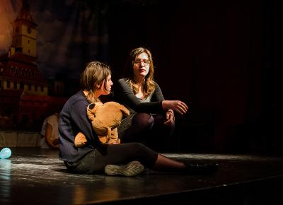 Two Romanian students appear on stage performing a play.