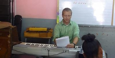Volunteer giving a piano lesson to a student on the Music project in Jamaica