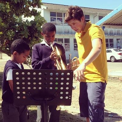Local South African school children learn how to play an instrument with a Projects Abroad volunteer.