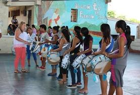 A volunteer and children practise their drumming set in Ecuador.