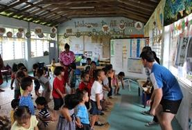 Volunteers on the Community Village Project in Samoa learn a dance from local children.