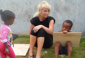 A volunteer assists young Jamaican children with their homework on the Maroon Community Project.