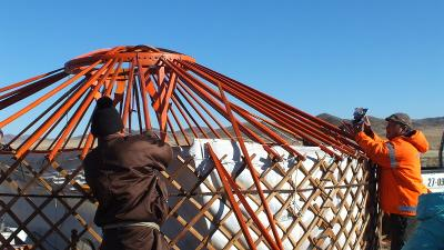 A local man building a new ger receives assistance from a volunteer on the Mongolian Steppe.