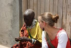 A volunteer learns about the Maasai way of life from a local Maasai woman in Tanzania.