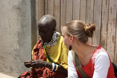 Volunteer and Maasai woman do crafts together in Tanzania, Africa