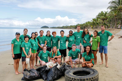 A group volunteers working together on a beach clean-up activity in Fiji