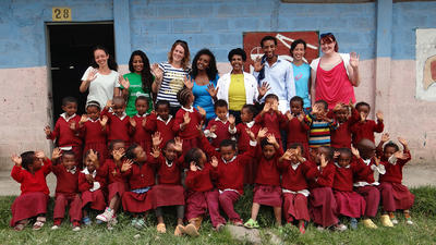 Group of students and teachers together at a school on a service learning trip to Africa