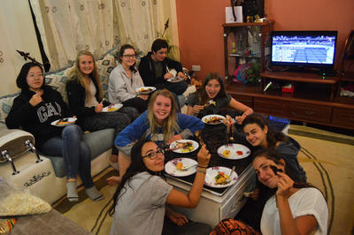 High school students enjoying dinner together at a host family in Kenya, Africa
