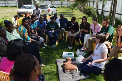 A medical student volunteering to teach CPR on a medical outreach in rural Africa
