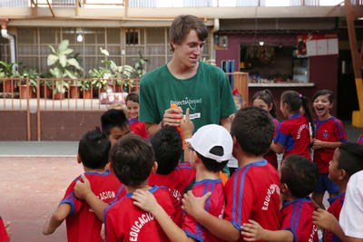 A student athlete volunteering abroad coaching a group of children in Costa Rica