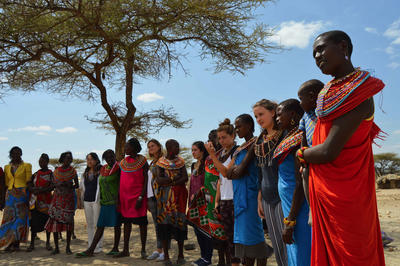 A group of college students on a service project interact with local people at a traditional village in Kenya, Africa