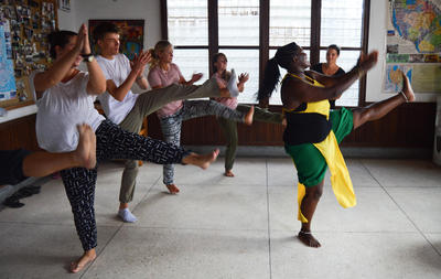 A group of volunteers in Tanzania, Africa learn traditional dance moves at the Projects Abroad office