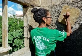 A volunteer plasters a wall for a new house in Jamaica over Easter.