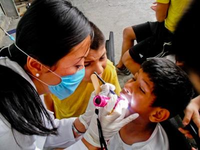 Dentistry intern checks up on a child in a dental outreach program