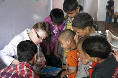 Indian children gather around a Projects Abroad medical intern in India
