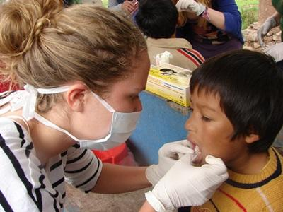 Dentistry Elective intern cleans teeth of a young boy in Peru