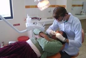 A Bolivan dentist performs a dental examination on a patient.