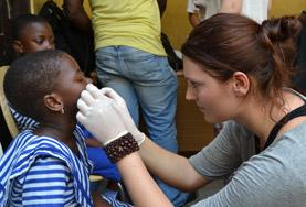 A volunteer examines a child's gums and teeth as part of her Dentistry School Elective in Ghana.