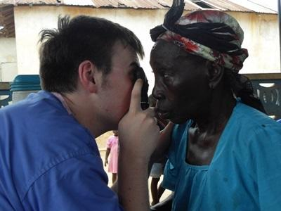 Medical elective volunteer performing an eye check for an elderly woman