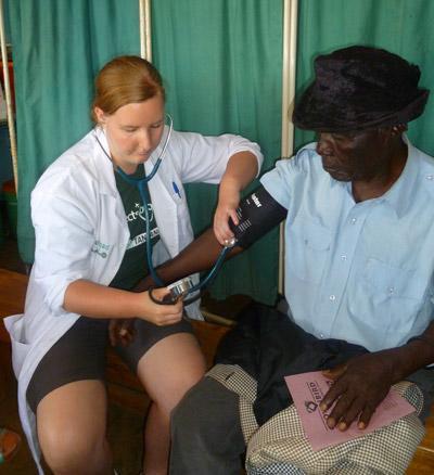 Medicine intern checks the blood pressure of a middle aged woman in Tanzania