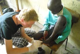 A Medical School Elective volunteer cleans a young boy's wound in Kenya.