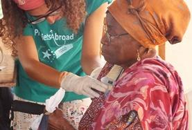 A woman in Togo gets her vitals checked by a volunteer on the Medical School Elective.