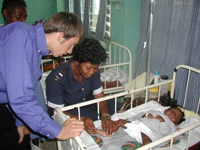 A Ghanaian nurse checks a baby's vitals while being observed by a Projects Abroad intern
