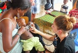 A newborn baby is held by a Midwifery School Elective student volunteering in Togo.