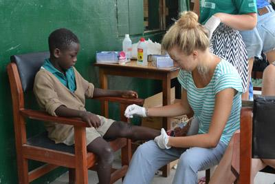 Nursing intern bandages up a young boy's knee in a medical outreach program in Ghana