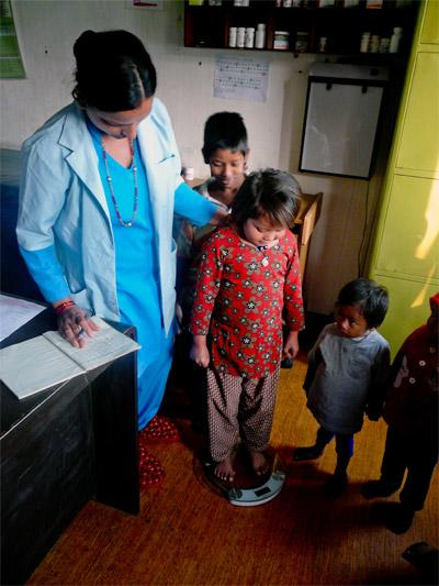 Nursing intern weights young children in a clinic on an Elective project in Nepal