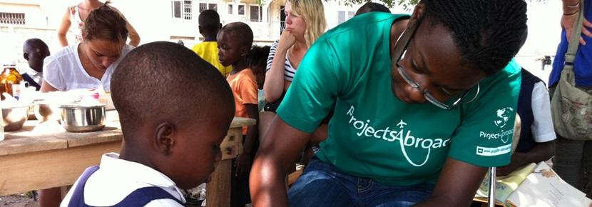 Nursing student bandages up a young boy in a community abroad
