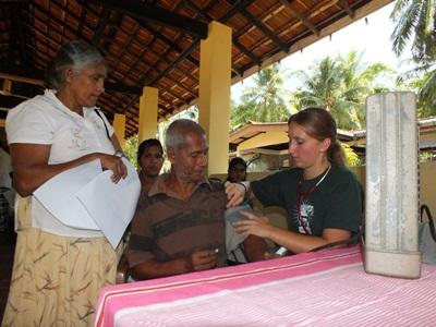 Nursing intern takes the blood pressure of an elderly man in a community outreach program in Sri Lanka