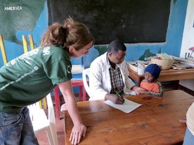 Nursing intern with local staff working with children in Tanzania