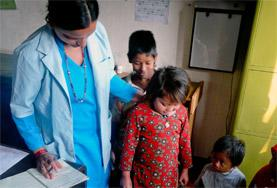 A Nursing School Elective volunteer helps weigh a child in Nepal as part of her project work.