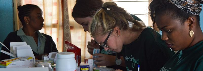 On an outreach project in Tanzania volunteers help with medicine dispensing