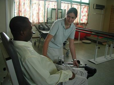 A Ghanaian patient receives physical therapy treatment from an intern