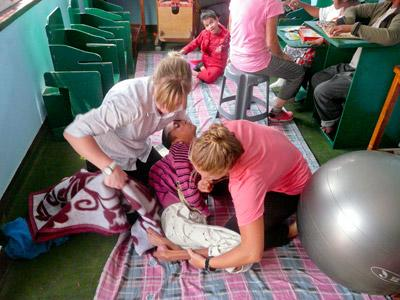 Two physical therapy elective interns assist a disabled child in a clinic in Morocco