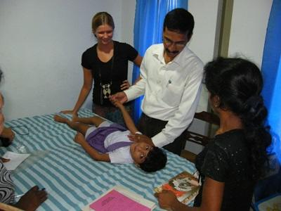 Physical Therapy staff and volunteers observe a session with a patient in a clinic in Sri Lanka