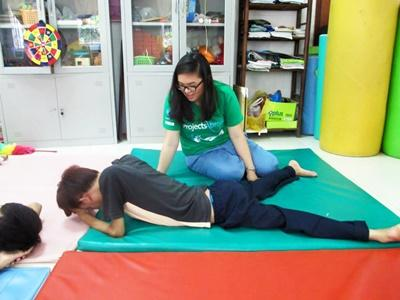 Projects Abroad intern assists with physical therapy exercises at a rehabilitation center in Vietnam, Asia.