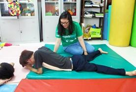 In Vietnam, a student on the Physical Therapy School Elective helps a man with his stretches on the floor.