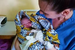 A Midwifery School Elective student holds a baby at her placement abroad.