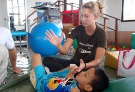 A Physical Therapy School Elective student assists a young child with his therapy.
