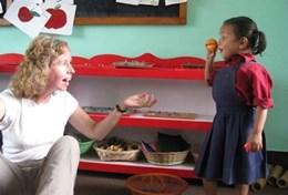 A Grown-Up Special volunteer on the Care & Community Project teaches a child about fruit in Nepal.