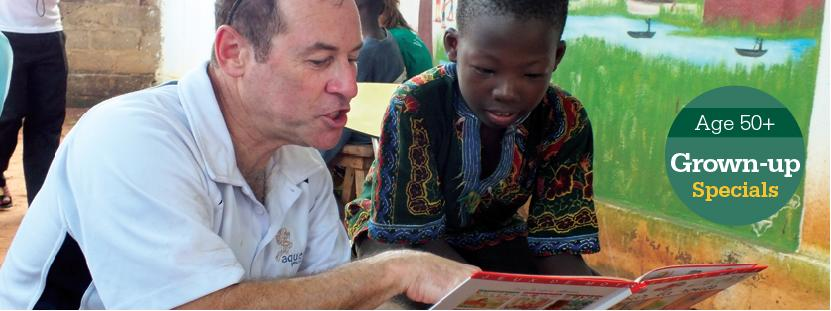 A child listens to an older Projects Abroad volunteer reading at a Care & Community placement.