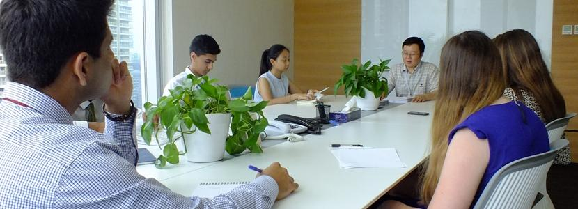 High School interns on the Business project sit in a business meeting overseas