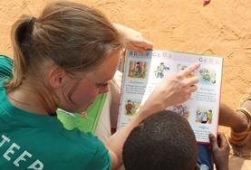 A Care & Community with French Project High School Special volunteer reads to a young boy in Togo.